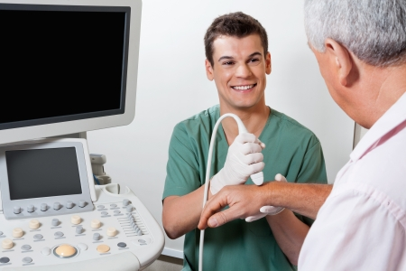 ultrasound: Happy Technician Scanning Male Patient s Hand Stock Photo