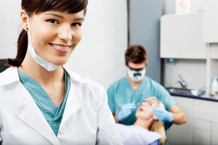 Female Hygienist With Dentist Working In The Background photo