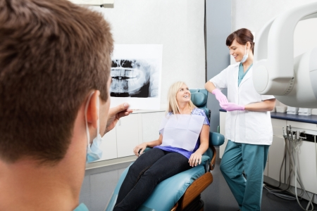 Dentist Examining X-Ray Image With Female Assistant Communicatin photo