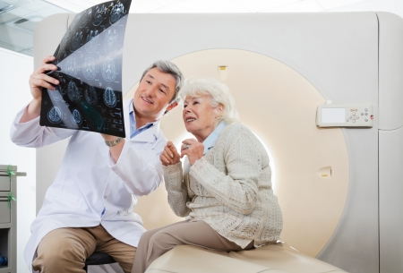 tomography: Doctor And Patient Looking At CT Scan X-ray