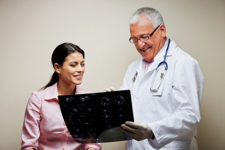 check up: Radiologist Showing X-ray To Patient Stock Photo