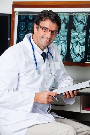 mri scan: Doctor Sitting At Desk With Clipboard