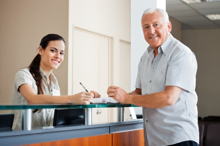 receptionist: Senior Man Standing At Hospital Reception Stock Photo