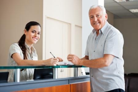 secretaria: Senior Man Standing At recepción del hospital Foto de archivo