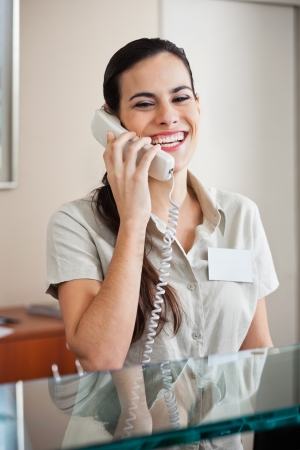 answering call: Happy Female Receptionist On Call Stock Photo