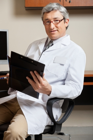 Mature Doctor Holding Clipboard photo