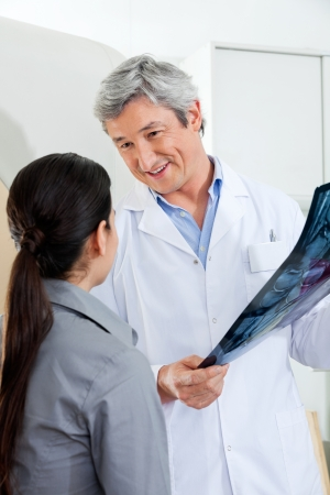 Radiologist Looking At Patient While Holding X-ray photo