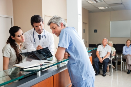 receptionist: Doctors Reviewing X-ray At Reception Stock Photo