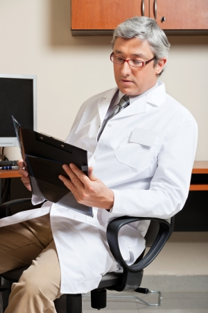 computer lab: Mature Male Doctor Reading Stock Photo