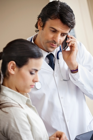Doctor Attending Call While Standing With Colleague photo