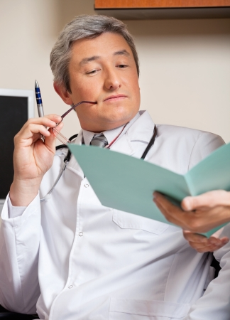 Doctor Reading Medical Report Stock Photo - 17213636