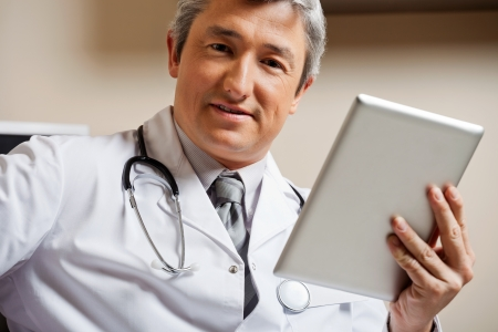 Male Doctor Holding Digital Tablet photo