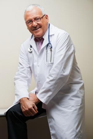 Senior Doctor Sitting On Desk Stock Photo - 17213604