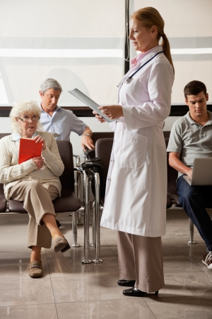 standing reception: Doctor Reading File With People In Lobby