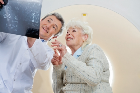 radiogram: Doctor With Patient Looking At MRI X-ray Stock Photo