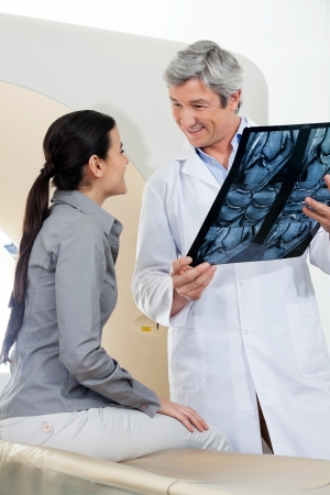 radiogram: Radiologist Looking At Female Patient Stock Photo