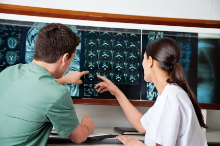cancer x ray: Medical Technicians Pointing At MRI X-ray