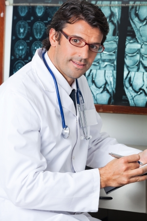 Male Doctor Sitting At Desk Stock Photo - 17238669