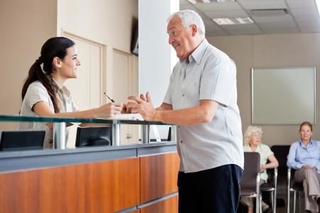 Hombre comunicación con Recepcionista Mujer