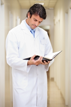 general knowledge: Doctor Reading Journal In Hospital Corridor