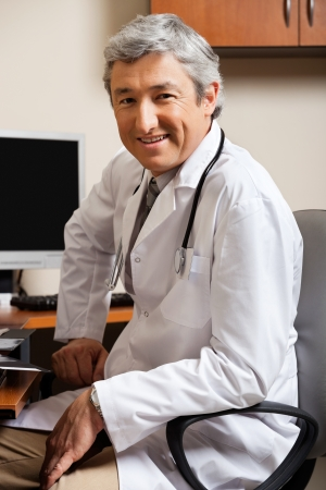 Male Doctor Sitting On Chair At Clinic Stock Photo - 17239254