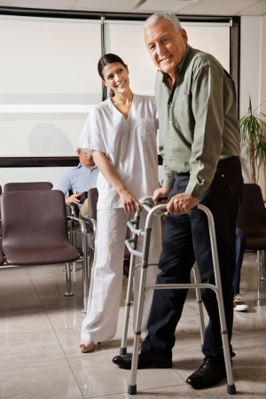 assistance: Female Nurse Helping Senior Patient With Walker Stock Photo