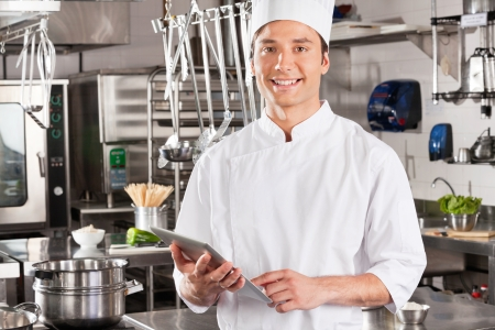 industrial kitchen: Happy Chef Holding Tablet Computer Stock Photo