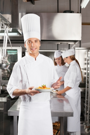 Confident Chef Presenting Dish In Commercial Kitchen photo