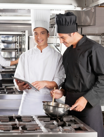 industrial kitchen: Chefs With Digital Computer Cooking Food