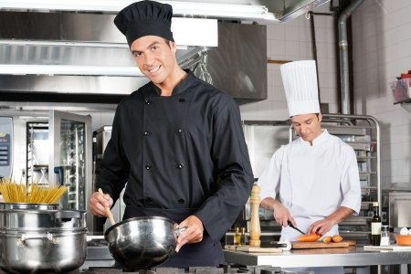 commercial kitchen: Chefs Cooking Food In Kitchen