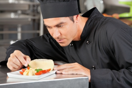 Male Chef Garnishing Dish photo