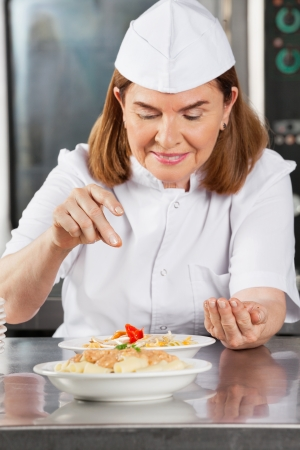 Female Chef Adding Spices To Dish photo