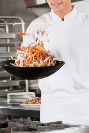 Chef Flipping Vegetables in Wok photo