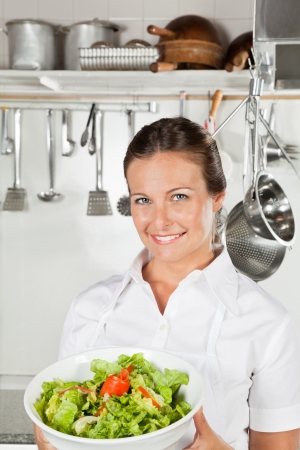 Female Chef Holding Bowl Of Salad photo