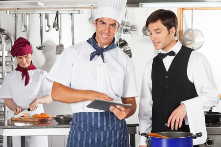 Chef With Waiter Using Digital Tablet photo