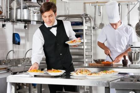 mesero: Camarero y cocinero que trabaja en cocina comercial Foto de archivo