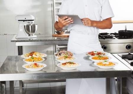 Chef Using Digital Computer In Kitchen Stock Photo - 18005883