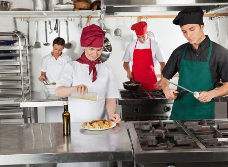 Chefs Working In Restaurant Kitchen photo