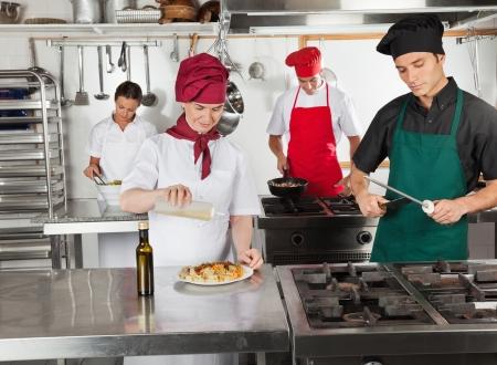 sharpening: Chefs Working In Restaurant Kitchen Stock Photo