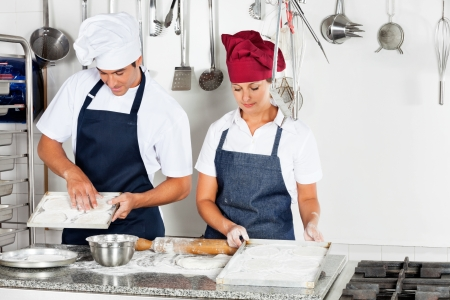 commercial kitchen: Chefs Baking At Kitchen Counter