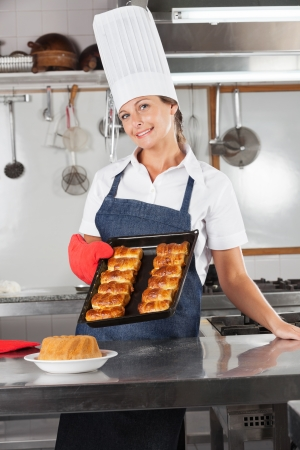 Female Chef Holding Tray Of Baked Breads Stock Photo - 18005907