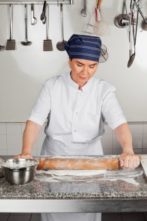 Female Chef Rolling Dough At Kitchen Counter Stock Photo - 18005904