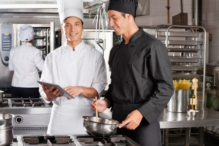 Chef Assisting Colleague In Preparing Food photo