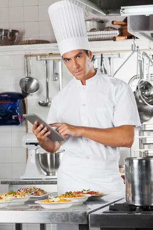 Chef Holding Tablet With Pasta Dishes At Counter photo