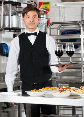 Waiter Holding Wineglasses on Tray photo
