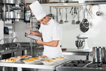 industrial kitchen: Chef With Clipboard Going Through Cooking Checklist Stock Photo