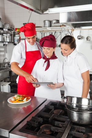 Chefs Looking For Recipe On Digital Tablet photo