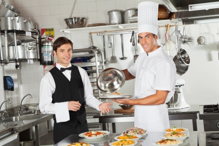 hotel staff: Waiter Taking Customer s Food From Chef Stock Photo
