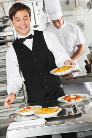 mesero: Camarero Pasta Holding Dish Foto de archivo