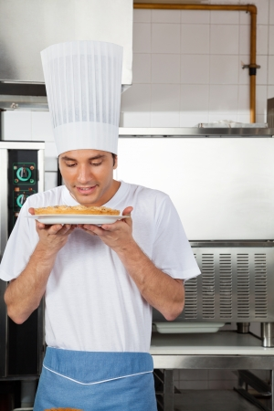 Chef Smelling Sweet Dish In Kitchen photo